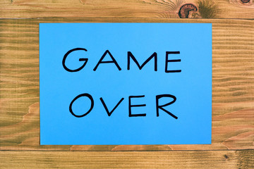 Blue paper with text game over on wooden table,relationship breakup concept.