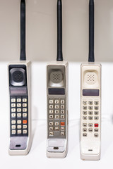 Three large vertical vintage old portable outdated cellphones phones standing on display with buttons