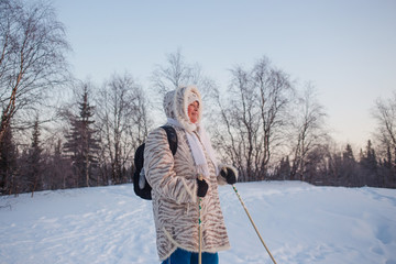 Happy senior woman looking to winter sunset in forest. Nordic walking activity
