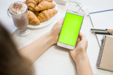 smartphone in the hands of a green screen in a cafe, smart phone with chroma key green screen on white background, new technology concept
