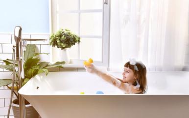 Happy little baby girl sitting in bath tub  in the bathroom