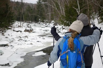 cross country skiers stop to enjoy the winter river view