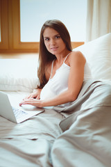Beautiful brunette lying on bed at home