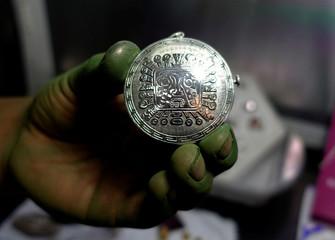 "A jewel artisan holds a silver piece at the ""Villa Imperial de Potosi"" jeweller's workshop in La Paz"