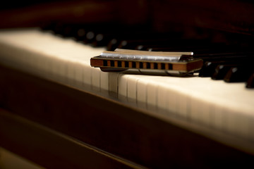 Close up macro photo of chromatic wooden harmonica on white piano keys, shallow focus