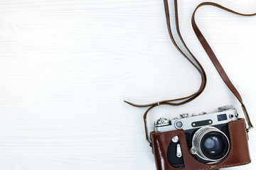 vintage old camera in leather case on white wooden table background
