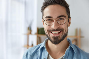 Close up shot of cheerful satisfied attractive male with stubble, has broad smile, wears round spectacles, rejoices success at work, stands against cozy interior. Fashionable designer glad be praised Wall mural