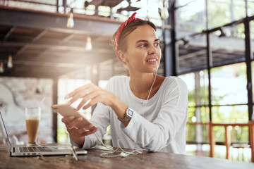 Fashionable lovely woman enjoys favourite music in earphones, uses modern electronic gadgets for entertainment and browsing internet, looks happily away, being always in touch. People and technlogy