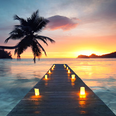 romantic beach with wooden jetty and lamps, romantic travel