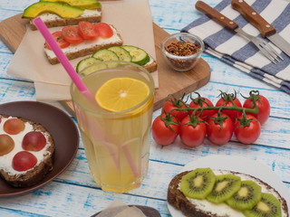 Sandwich with ovaries, with avocado, with tomato and cucumber, with kiwi, grapes and glass of lemonade on the table.