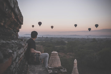 Silhouette of young male backpacker sitting and watching hot air balloon travel destinations in Bagan, Myanmar.