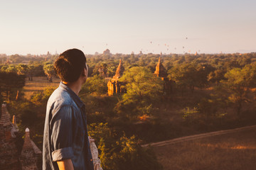 Silhouette of young male backpacker watching sunset and pagoda in Bagan, Burma.