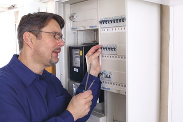 Elektriker hantiert an Sicherungskasten