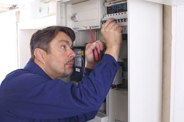 Elektroinstallateur schraubt an Sicherungskasten
