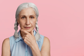 Portrait of beautiful mature woman keeps hand under chin, looks with clever and wise expression at camera, going to have walk in park, thinks what to wear, isolated over pink studio background