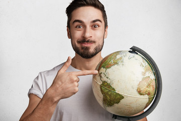 Positive brunet male traveller chooses place to go on earth, holds world globe, isolated over white background. Young attractive successful male boasts to travel much, shows new destinations