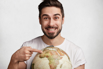 Indoor shot of smiling glad male student rejoices coming holidays, indicates at one place on globe, happy to have vacations abroad, ready exploring new places, poses against white background
