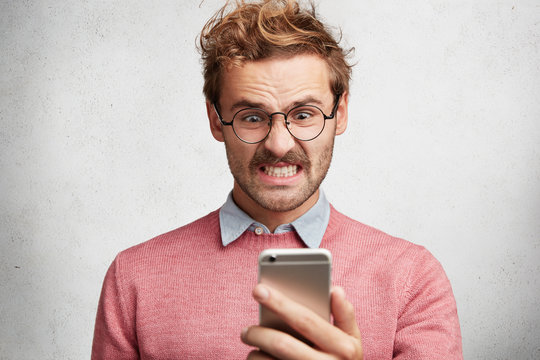 Angry irritated male reads text message on smart phone remind him about bills, needs to pay debts immediately, frowns face in dissatisfaction, expresses big rage and displeasure, blows steam