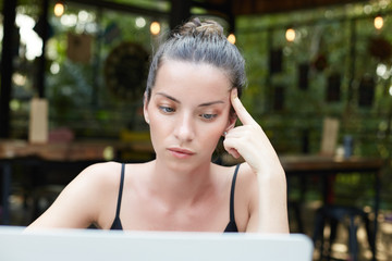 Portrait of beautiful mixed race brunette woman with well-shaped eyebrows, green shining eyes and full lips touching temple thoughtfully, having hair in bun sitting at modern cafe working with laptop.