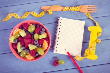 Fruit salad, tape measure with dumbbells and notepad for writing notes, healthy lifestyle and nutrition concept