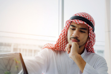 young Arabian business man developing a new idea and working with laptop computer on desk at the morning in home office, successful, financial, business technology and investment concept