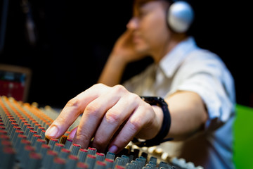 sound engineer hands working on audio mixing console in recording, broadcasting studio