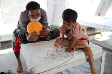 A Rohingya refugee child who suffers from diphtheria colors a drawing book while admitted in Samaritan's Purse diphtheria clinic in Cox's Bazar