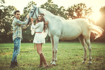 Young happy couple and beautiful horse
