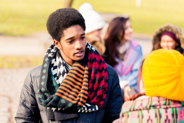 African American young man talking with a female friend outdoors in a winter day
