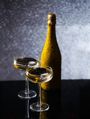 Festive photo of bottle of champagne in gold wrapper with two wine glasses