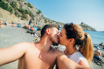 couple of travelers taking selfies and kissing on the beach on sea background