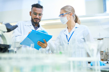 International team of scientists working together in medical laboratory doing research on  chemicals and bacteria
