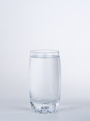 Glass of water with condensated drops on white background