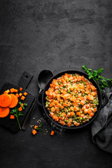 Carrot braised with fresh green peas in creamy milk sauce in stewpan, vegetable saute on black background, top view