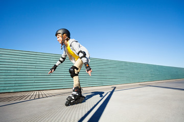 Boy rollerblading in helmet and protective gear