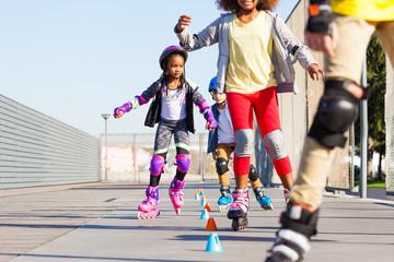 Kids learning to slalom skate with inline skates
