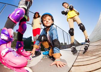Cute boy in roller skates having fun with friends