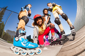 African girl rollerblading with friends outdoors