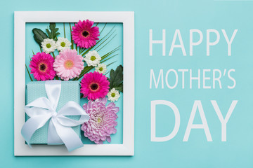Happy Mother's Day Pastel Candy Colors Background. Floral mothers day flat lay minimal concept with beautifully wrapped present.
