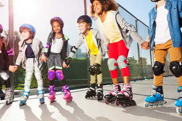 Happy friends rollerblading together at sunny day
