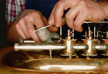 a craftsmen adjusts a brass instrument