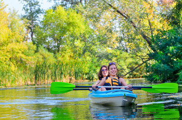 Family kayaking sport, mother and child paddling in kayak on river canoe tour, active autumn weekend and vacation, fitness concept