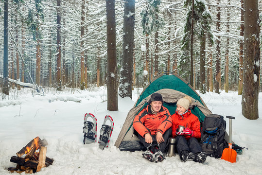 a couple on an expedition in the winter mountains and the forest, a break for tea