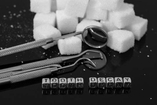Dentist tools and mirror with sugar cubes and the words tooth decay on beads