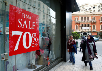 People walk past a clothing store window with placards announcing discounts for winter sales, in Cairo