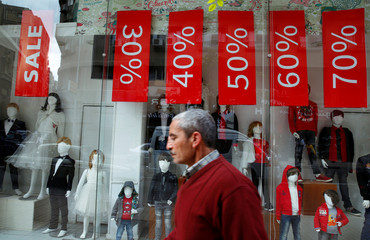A man walks past a clothing store window with placards announcing discounts for winter sales, in Cairo