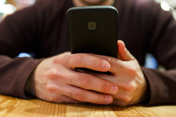Photo of man with smartphone in hands, sitting at table