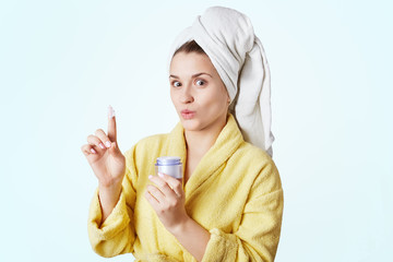 Pretty young woman going to make mask on face after taking shower, holds bottle with cream in hand, demonstares it on finger, dressed in bathrobe and towel on head, isolated over white bakground