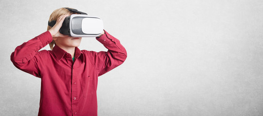 Horizontal shot of small boy wears VR glasses, sees virtual reality, isolated over white background with copy space for advertising content. Male child in virtual headset glasses. Future, progress
