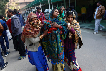 Relatives of a victim, who was who was killed in Saturday's fire in a warehouse, mourn as they wait outside a hospital in New Delhi